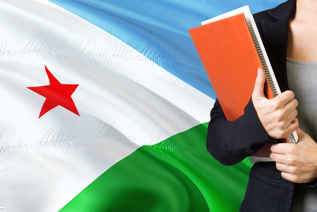 Learning language concept. Young woman standing with the Djibouti flag in the background. Teacher holding books, orange blank book cover.