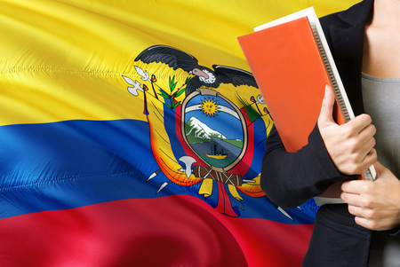 Learning Ecuadorean language concept. Young woman standing with the Ecuador flag in the background. Teacher holding books, orange blank book cover. Banco de Imagens