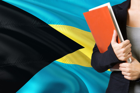 Learning Bahamian language concept. Young woman standing with the Bahamas flag in the background. Teacher holding books, orange blank book cover. 版權商用圖片