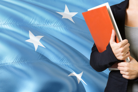 Learning Micronesian language concept. Young woman standing with the Micronesia flag in the background. Teacher holding books, orange blank book cover.