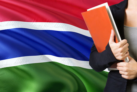 Learning Gambian language concept. Young woman standing with the Gambia flag in the background. Teacher holding books, orange blank book cover.