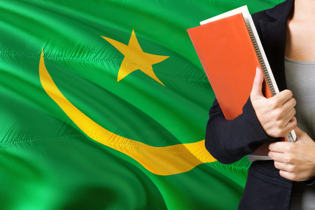Learning Mauritanian language concept. Young woman standing with the Mauritania flag in the background. Teacher holding books, orange blank book cover.