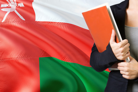 Learning Omani language concept. Young woman standing with the Oman flag in the background. Teacher holding books, orange blank book cover.