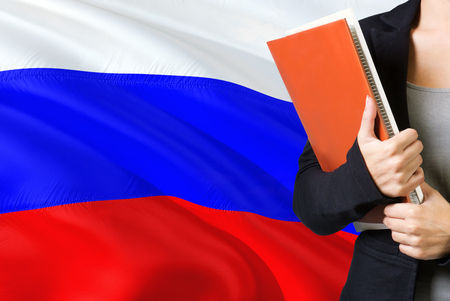 Learning Russian language concept. Young woman standing with the Russia flag in the background. Teacher holding books, orange blank book cover. 版權商用圖片