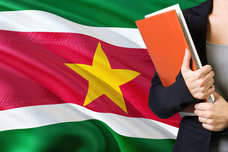 Learning Surinamese language concept. Young woman standing with the Suriname flag in the background. Teacher holding books, orange blank book cover.