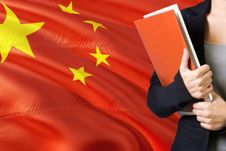 Learning Chinese language concept. Young woman standing with the China flag in the background. Teacher holding books, orange blank book cover.