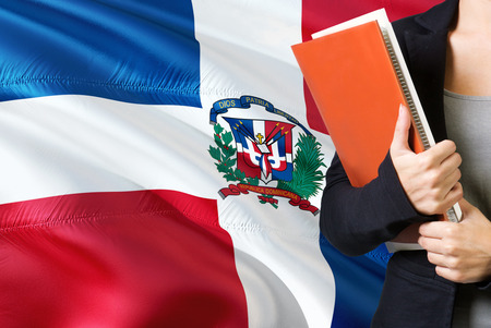 Learning Dominican language concept. Young woman standing with the Dominican Republic flag in the background. Teacher holding books, orange blank book cover.