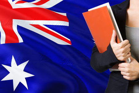 Learning Australian language concept. Young woman standing with the Australia flag in the background. Teacher holding books, orange blank book cover. 版權商用圖片