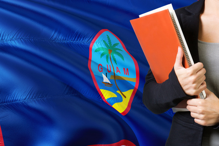 Learning language concept. Young woman standing with the Guam flag in the background. Teacher holding books, orange blank book cover.