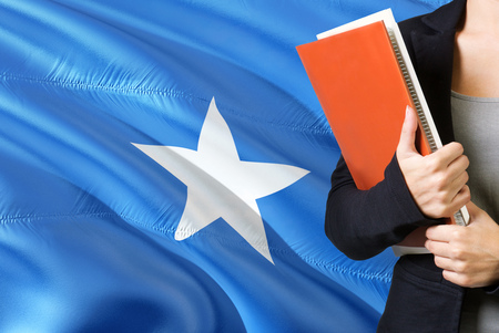 Learning Somalian language concept. Young woman standing with the Somalia flag in the background. Teacher holding books, orange blank book cover. Stok Fotoğraf