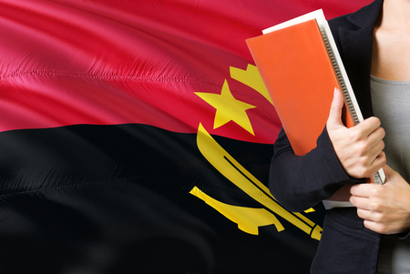 Learning Angolan language concept. Young woman standing with the Angola flag in the background. Teacher holding books, orange blank book cover.