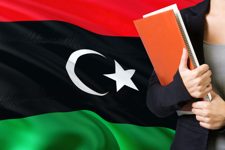 Learning Libyan language concept. Young woman standing with the Libya flag in the background. Teacher holding books, orange blank book cover.