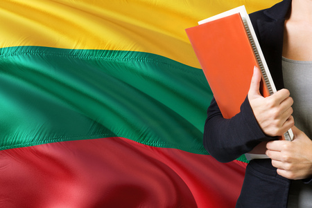 Learning Lithuanian language concept. Young woman standing with the Lithuania flag in the background. Teacher holding books, orange blank book cover. 版權商用圖片