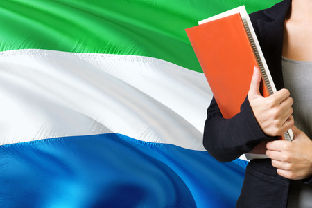 Learning language concept. Young woman standing with the Sierra Leone flag in the background. Teacher holding books, orange blank book cover.
