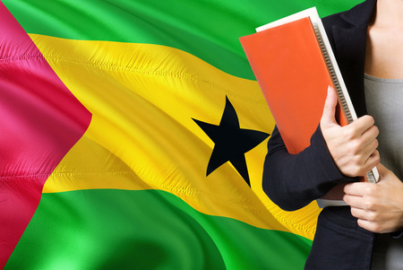 Learning language concept. Young woman standing with the Sao Tome And Principe flag in the background. Teacher holding books, orange blank book cover.