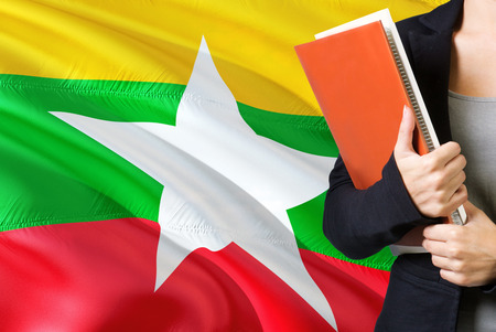 Learning Burmese language concept. Young woman standing with the Myanmar flag in the background. Teacher holding books, orange blank book cover.