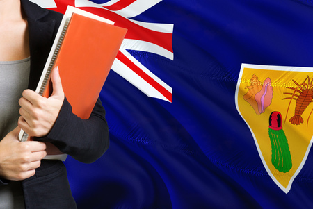 Learning language concept. Young woman standing with the Turks And Caicos Islands, flag in the background. Teacher holding books, orange blank book cover.