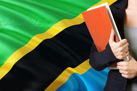 Tansanisches Sprachkonzept lernen. Junge Frau, die mit der Tansania-Flagge im Hintergrund steht. Lehrer, der Bücher hält, orange leerer Bucheinband. Standard-Bild