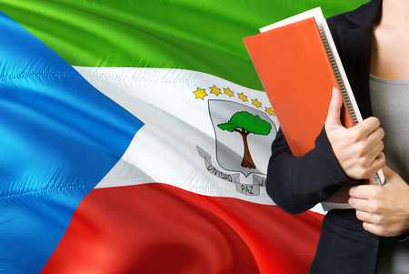 Learning language concept. Young woman standing with the Equatorial Guinea flag in the background. Teacher holding books, orange blank book cover.