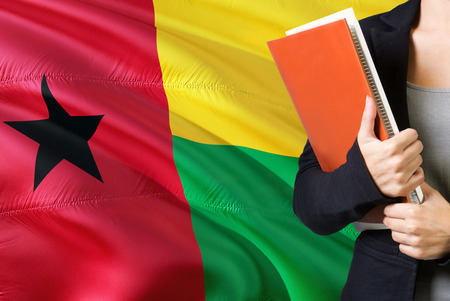 Learning language concept. Young woman standing with the Guinea Bissau flag in the background. Teacher holding books, orange blank book cover. Фото со стока