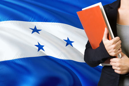 Learning Honduran language concept. Young woman standing with the Honduras flag in the background. Teacher holding books, orange blank book cover. 版權商用圖片