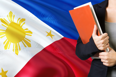 Learning Filipino language concept. Young woman standing with the Philippines flag in the background. Teacher holding books, orange blank book cover.
