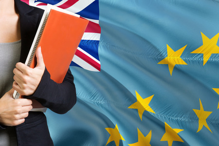 Learning Tuvaluan language concept. Young woman standing with the Tuvalu flag in the background. Teacher holding books, orange blank book cover.