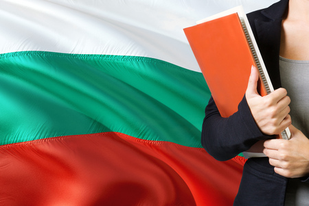 Learning Bulgarian language concept. Young woman standing with the Bulgaria flag in the background. Teacher holding books, orange blank book cover.
