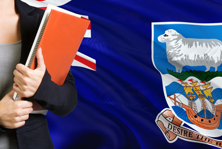 Learning language concept. Young woman standing with the Falkland Islands flag in the background. Teacher holding books, orange blank book cover.