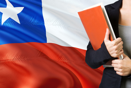Learning Chilean language concept. Young woman standing with the Chile flag in the background. Teacher holding books, orange blank book cover. 版權商用圖片