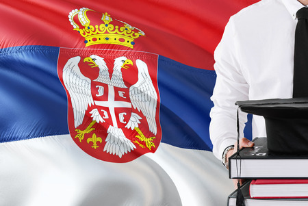 Successful Serbian student education concept. Holding books and graduation cap over Serbia flag background. Zdjęcie Seryjne