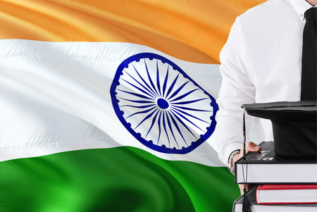 Successful Indian student education concept. Holding books and graduation cap over India flag background.