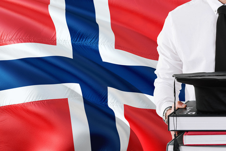 Successful Norwegian student education concept. Holding books and graduation cap over Norway flag background.