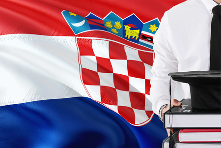 Successful Croatian student education concept. Holding books and graduation cap over Croatia flag background.