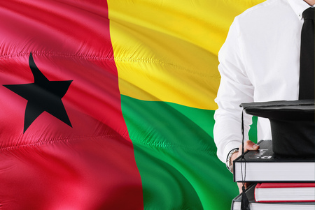 Successful student education concept. Holding books and graduation cap over Guinea Bissau flag background.