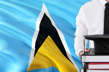 Successful student education concept. Holding books and graduation cap over Saint Lucia flag background.