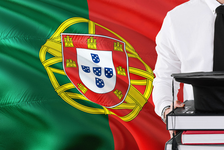 Successful Portuguese student education concept. Holding books and graduation cap over Portugal flag background.