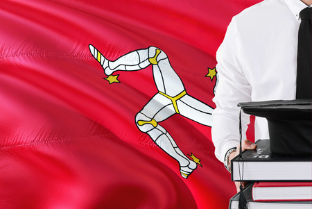 Successful student education concept. Holding books and graduation cap over Isle Of Man flag background.