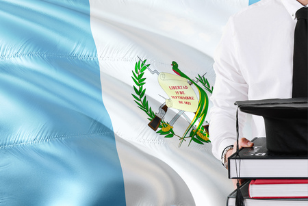 Successful Guatemalan student education concept. Holding books and graduation cap over Guatemala flag background.