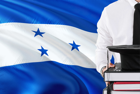 Successful Honduran student education concept. Holding books and graduation cap over Honduras flag background.