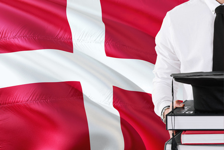 Successful Danish student education concept. Holding books and graduation cap over Denmark flag background.