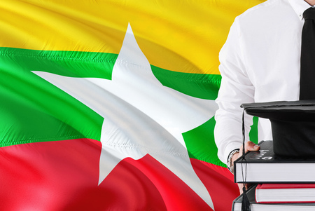 Successful Burmese student education concept. Holding books and graduation cap over Myanmar flag background.