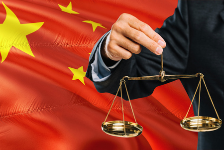 Chinese Judge is holding golden scales of justice with China waving flag background. Equality theme and legal concept.