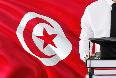 Successful Tunisian student education concept. Holding books and graduation cap over Tunisia flag background.