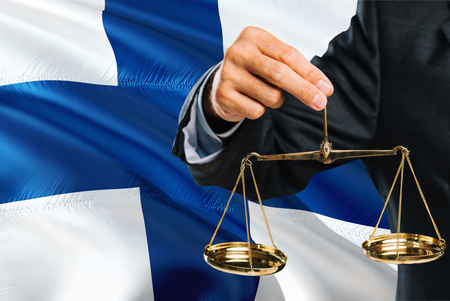 Finnish Judge is holding golden scales of justice with Finland waving flag background. Equality theme and legal concept.