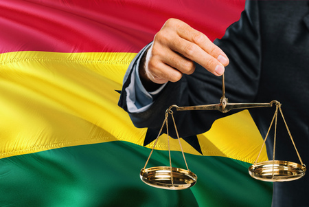Ghanaian Judge is holding golden scales of justice with Ghana waving flag background. Equality theme and legal concept.
