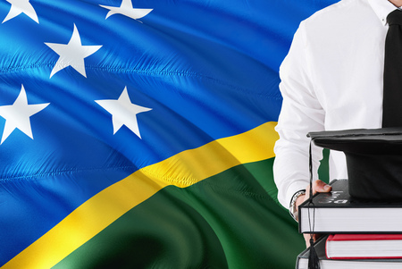 Successful student education concept. Holding books and graduation cap over Solomon Islands flag background.