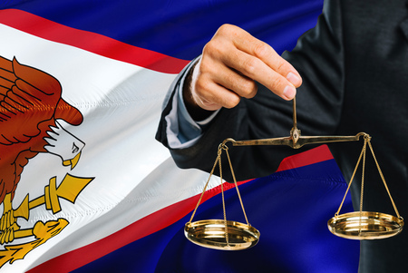 Judge is holding golden scales of justice with American Samoa waving flag background. Equality theme and legal concept.