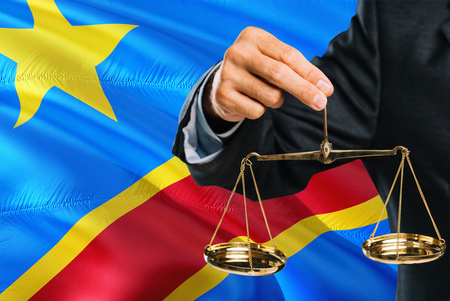 Congolese Judge is holding golden scales of justice with Congo waving flag background. Equality theme and legal concept.