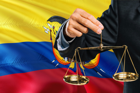 Ecuadorean Judge is holding golden scales of justice with Ecuador waving flag background. Equality theme and legal concept. Banco de Imagens
